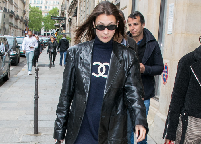 Bella Hadid Takes The Logo Obsession to a Classy Level Logo Chanel Dress, leather jacket, sheer tights and black boots