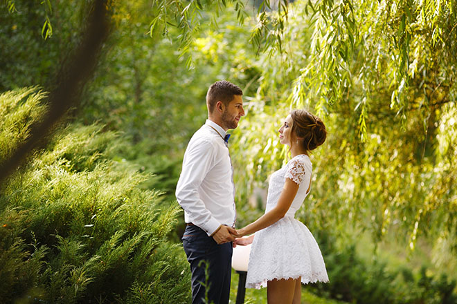how-to-wear-a-short-wedding-dress-bride-with-short-dress-holding-grooms-hand