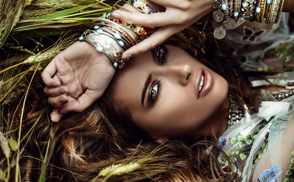 Beautiful hippie girl lying in a grass. Modern boho style. Beauty, fashion,