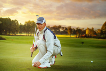 male golf player is putting off a ball from hole