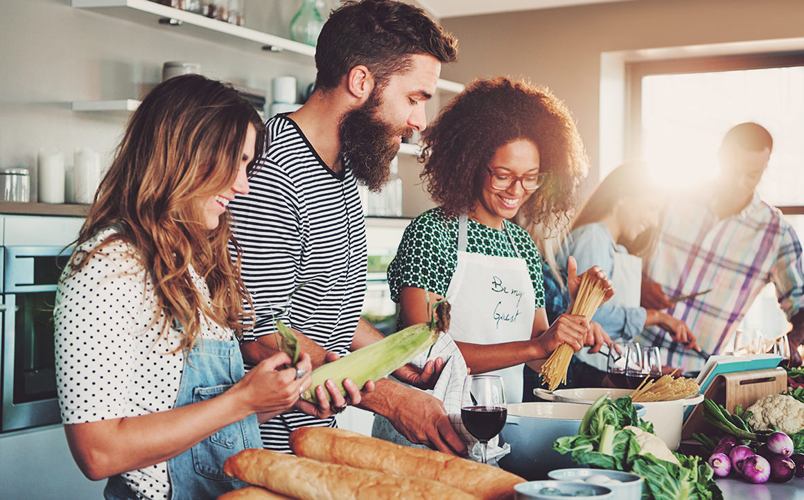 Good friends laughing and talking while preparing meals at table full of vegetables and pasta ready for cooking in kitchen