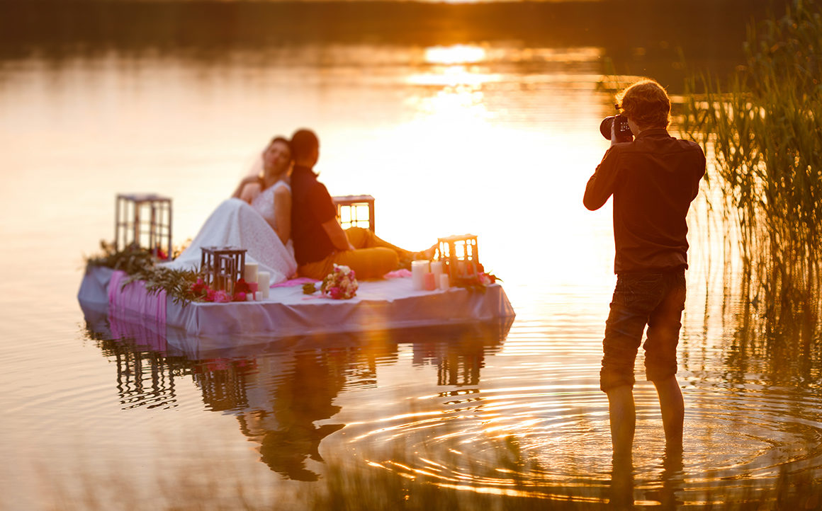Wedding photographer in action, taking a picture of the bride and groom sitting on the raft. Summer, sunset.