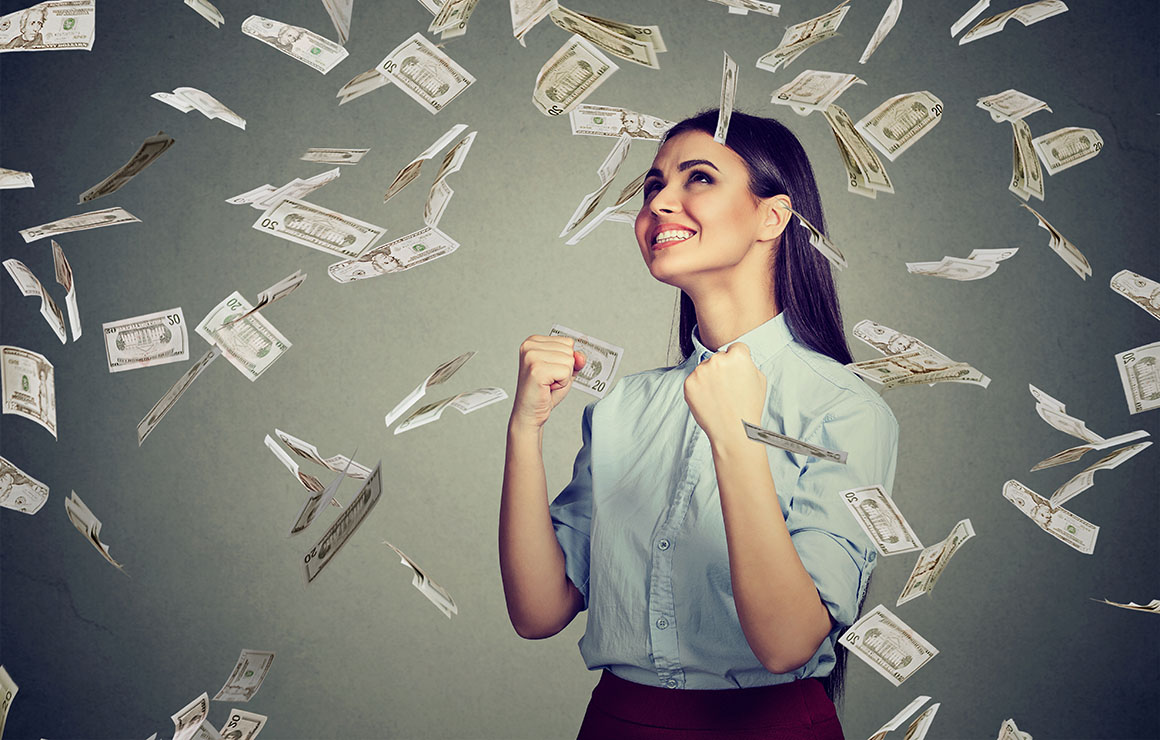 Portrait happy woman exults pumping fists ecstatic celebrates success under a money rain falling down dollar bills banknotes isolated on gray wall background with copy space