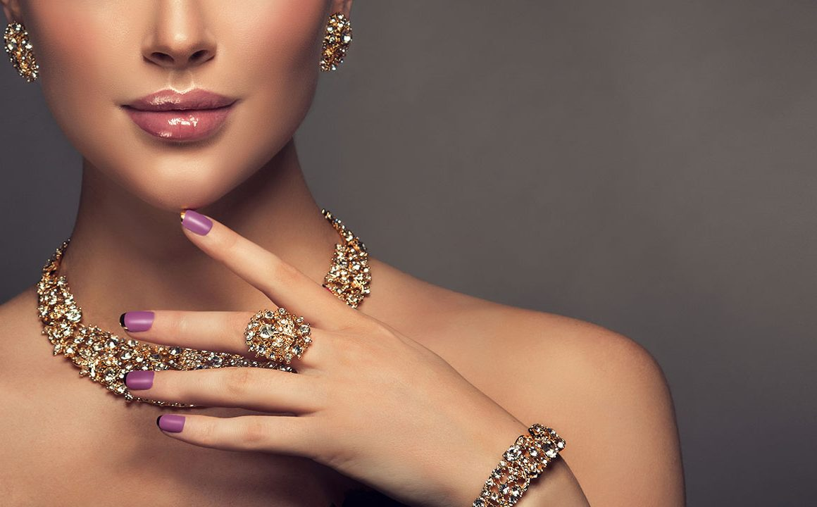 woman-holding-her-finger-to-her-face-showing-ring-bracelet-and-diamond-jewelry