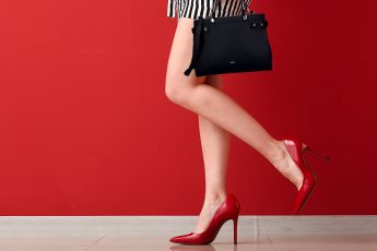 Young woman in high-heeled shoes near color wall