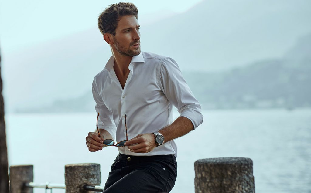 Stylish man in white classic shirt, looking at the mountains view