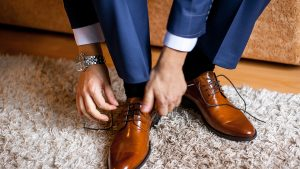 A man ties up his shoelaces on his brown shoes