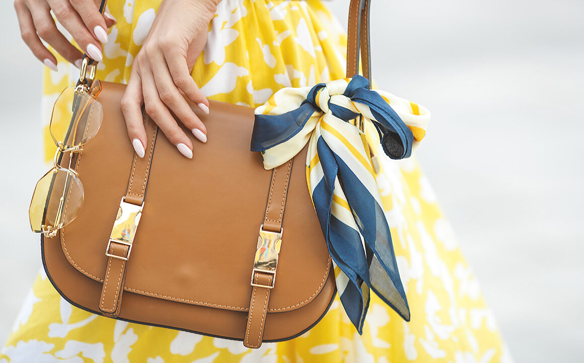 skincare-essentials-every-handbag-needs-woman-in-yellow-with-handbag-main-image