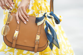 skincare-essentials-every-handbag-needs-woman-in-yellow-with-handbag-main-image