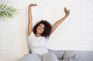 how-sleep-affects-your-physical-health-happy-woman-stretching