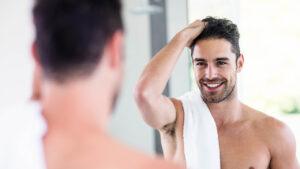 self-care-tips-for-men-man-grooming-his-beard-smiling