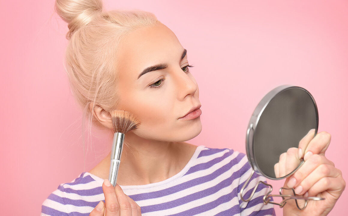 can-i-use-any-foundation-with-an-airbrush-machine-blonde-woman-applying-foundation-pink-backdrop