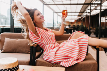 how-our-clothing-defines-us-woman-in-cute-dress-drinking-wine-happy