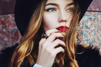 is-hifu-for-you-benefits-woman-looking-off-in-distance-in-red-lipstick-and-hat
