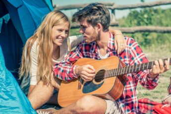 young-love-young-couple-camping-while-man-plays-guitar-1000x600