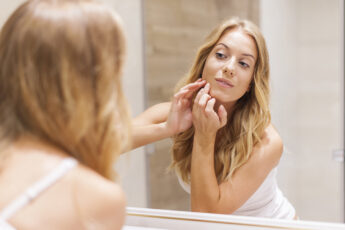 facial-serum-what-you-need-to-know-woman-looking-at-face-in-mirror