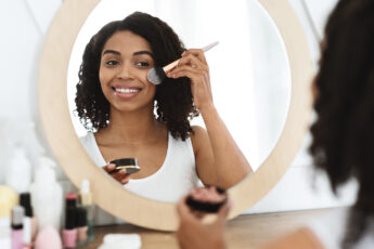 tips-to-achieve-perfect-makeup-every-time-girl-putting-on-makeup-in-mirror-main-image