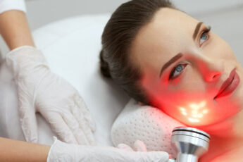 should-i-try-red-light-therapy-woman-getting-red-light-on-face