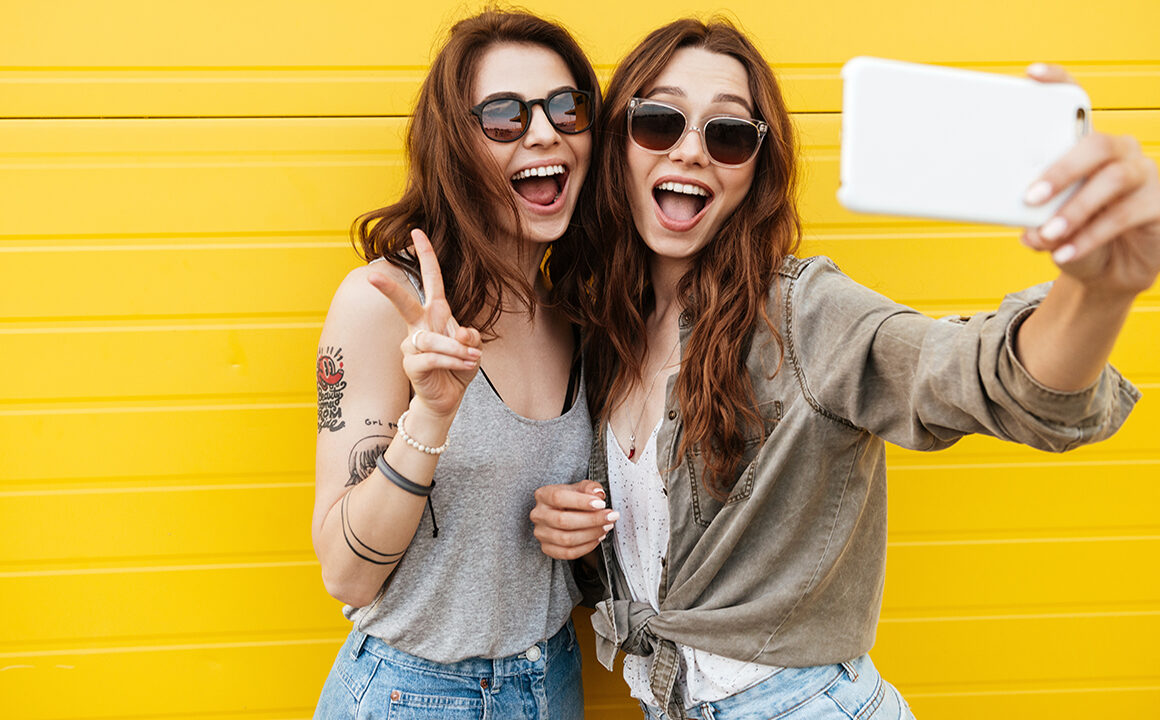 sprint-2021-fashion-essentials-trends-two-happy-friends-taking-selfie