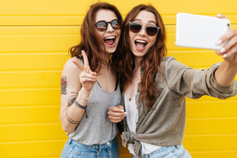 sprint-2021-fashion-essentials-trends-two-happy-friends-taking-selfie