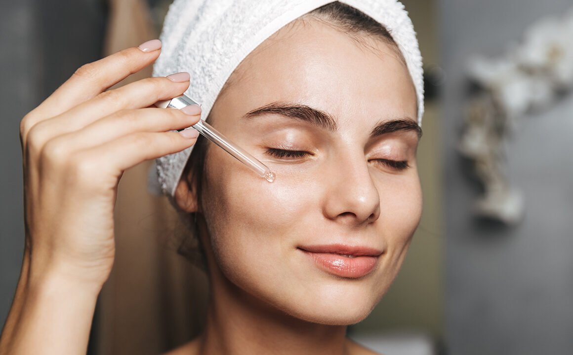 best-scar-reducing-treatments-woman-applying-facial-oil-happy-skincare