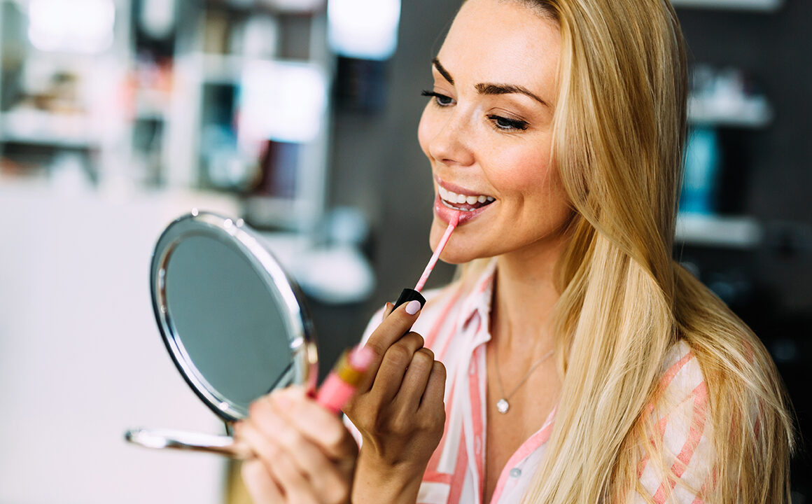 must-try-fashion-and-beauty-trends-woman-applying-lip-gloss-main-image