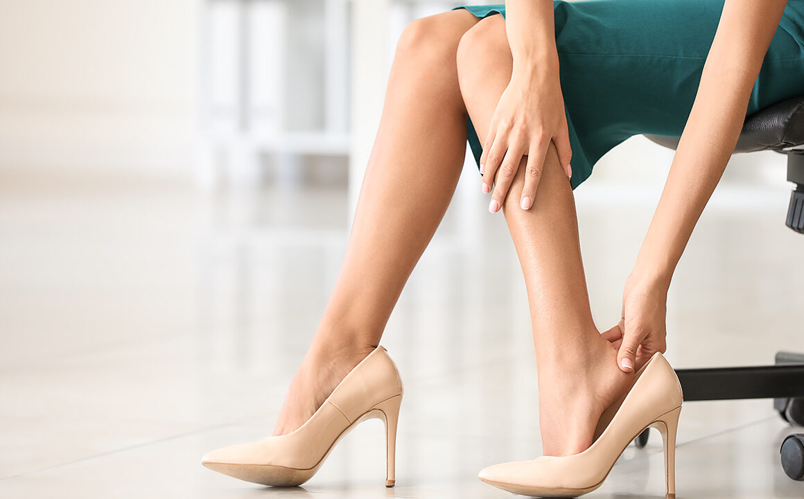 tips-to-avoid-foot-pain-when-wearing-heels-woman-holding-feet