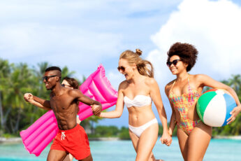 vacation-hair-fashion-group-of-friends-running-on-beach-main-image