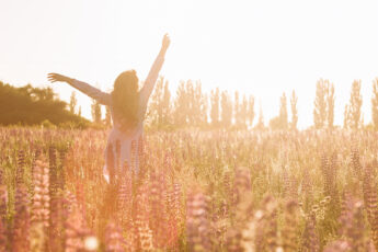 how-to-boost-your-confidence-happy-woman-frolicking-in-field